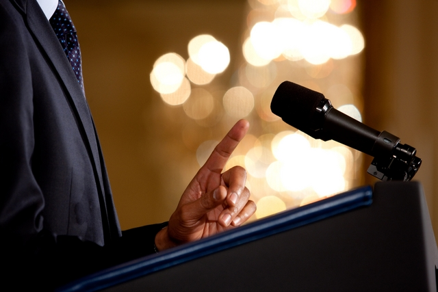 0519-0908-0820-3533_close_up_of_a_man_making_a_point_during_a_speech_microphone_and_podium_in_view_m